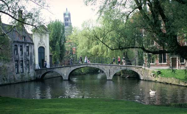 Photo shows an old stone bridge with three arches across a stream.
