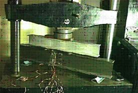 Photo shows an I-beam section in a metal machine applying a large compressive force.