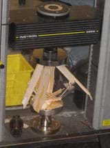 Photo shows a balsa wood structure crushed and splintered inside a glass box.