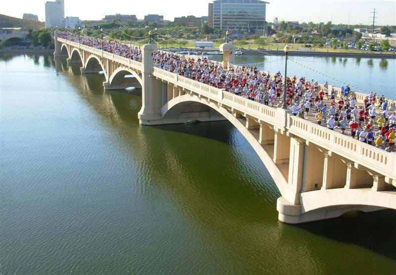 Photos shows mobs of people running a race over a white and graceful concrete bridge.
