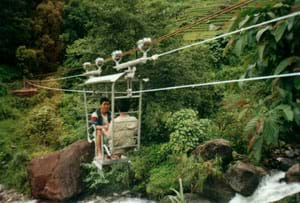 Photo shows two people sitting and facing each other in a metal-cage cable car that is hanging from pulleys resting on a steel wire strung across a river.