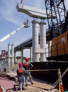 Construction site photo shows a crane placing a beam of concrete atop two concrete columns.