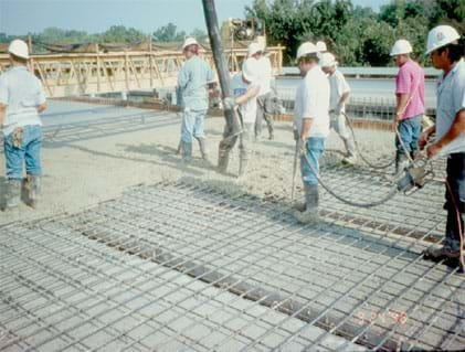 Photo shows men in construction hats and rubber boots walking on a metal grid.
