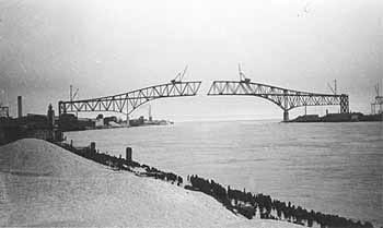 Black and white photo shows silhouette of two truss-type bridge spans being built from each side of a river, not yet meeting in the middle.