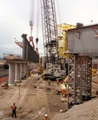 Photo shows a construction site with steel and concrete members, cranes, equipment and workers in hard hats.