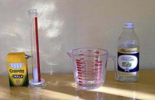 Photo shows a box of chalk, a graduated cylinder, a measuring glass and a bottle of vinegar.
