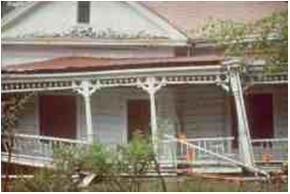 A picture of a house damaged by an earthquake. The front porch of the house appears to be lopsided and ready to fall over.