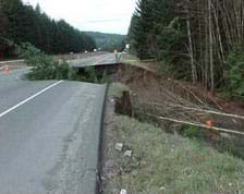 Photo shows a highway with an enormous sunken crater, large enough to fit a semi truck.