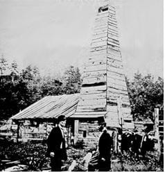 A black and white photo of a tall wooden building with people standing around it.