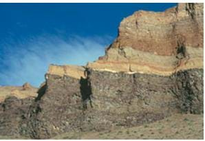 A cliff formation with layered sedimentary rocks.