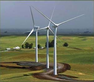 A photograph of wind turbines, also known as a wind farm. Blowing wind causes a turbine to rotate, turning an electric motor which makes electricity.