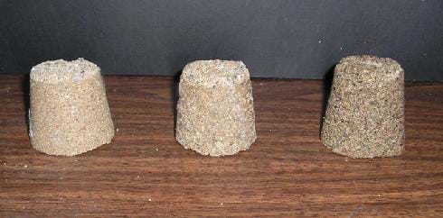 Photo shows three self-standing cup-shaped structures made from sand, water and/or glue. They have slightly different colors and textures.