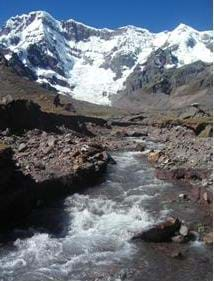 Photograph of a large mountain covered in snow (glacier) with a glacial stream flowing down valley of the mountain.