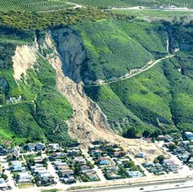 Photograph of a large landslide caused by water erosion. Shown is town at the base of a mountain that has partially collapsed. Many of the town's structures are completely or partially covered by dirt from the mountain landslide.