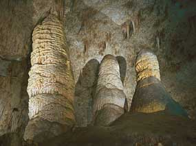 Photograph shows inside of a white stone cave with formations piled up from the floor and hanging down from the ceiling.