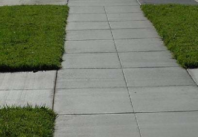 Photograph of a sidewalk with many vertical and horizontal grooves cut into the concrete.