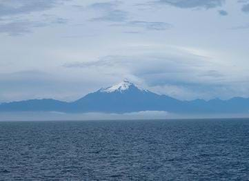 A photograph shows a vast sea in the foreground with a pointed, snow-capped, blue-tinted mountain on the distant shore.