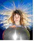 This photograph shows the surprise in a young girl's face and her long hair standing on end around her head as she touches a large, shiny silver orb in front of her.