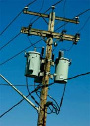 A photograph of a telephone pole, showing the top half of the pole with the connecting and draping wires and green glass insulators against a background of a blue sky.