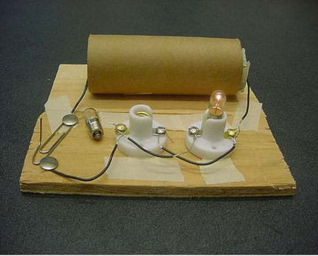 A photograph of a parallel circuit made with two D-cell batteries, two light bulb holders, two light bulbs and a switch. The two D-cell batteries are contained within a cardboard paper towel tube. One wire leads from the tube to the switch, which is made from two thumbtacks and a paper clip. Another wire exits the opposite end of the tube and is connected to one of the light bulb holders. The two light bulb holders are connected in parallel using short wires. The switch is closed. Although one light bulb is removed from its holder, the remaining light bulb is still lit.