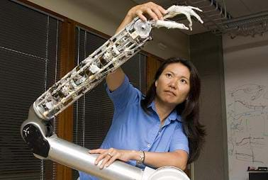 A photograph of a woman standing in front of a prosthetic arm controlled using robotics.