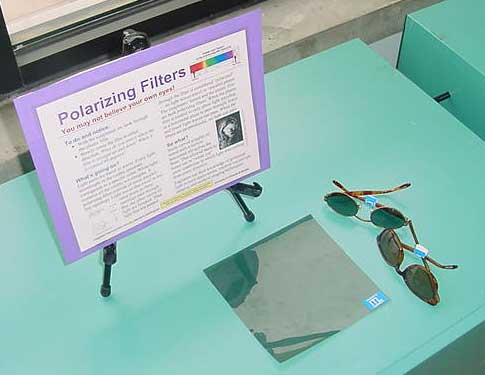 Photograph of sunglasses and a sheet of plastic.
