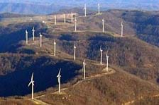 Photograph of 18 wind turbines located on a mountain ridge.