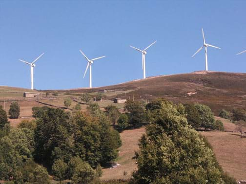 A landscape photo shows four, white, electricity-generating wind turbines on a hillside.