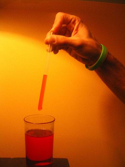 A finger plugs the top of a clear straw, causing red-colored water to stay in the straw.