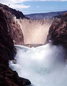 A photograph shows a huge concrete dam and water spraying below it.