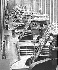 A black and white photo shows a row of huge steel turbines with ladders.
