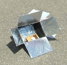 A photo shows a box with flaps covered in foil, and chocolate and marshmallows on a graham cracker inside the box.