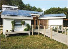 Photo of a small, modern home with photovoltaic panels on its angled rooftop.