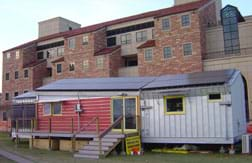 A photograph shows a modern mobile-home-size structure in front of a huge university building.