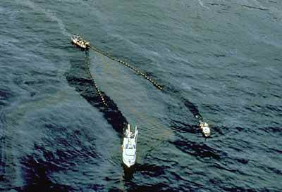 Arial photograph of two boats dragging a net through the ocean waters, skimming oil off the water surface of Prince William Sound.