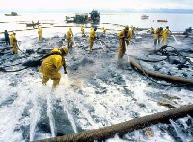 A photograph shows people in yellow protective clothing along the sandy shoreline hauling hoses and spraying oiled rocks with high pressure water.