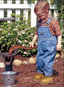 Photo shows a younge boy in denim overalls and work boots, pumping water from an old-fashioned well.