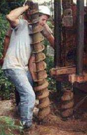 Photo shows a man drilling a hole in the ground with a drill (auger) that is as big as he is.