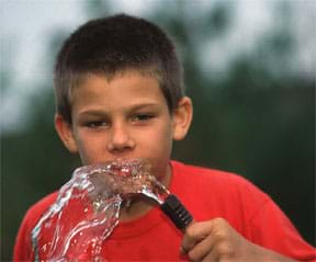 A photograph of a small boy, wearing a red t-shirt, drinking water from a garden hose.