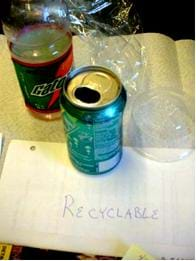 Photo shows a plastic drink bottle, aluminum soda can, plastic wrap and a plastic container, all depicting recyclable trash.