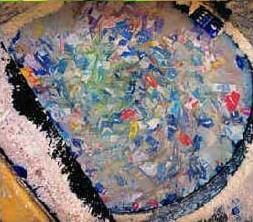 A photograph shows a big vat with hundreds of juice boxes soaking in water in an attempt to separate the paper, aluminum and plastic layers of the boxes.