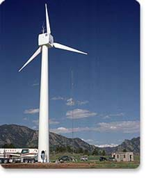 A photograph shows a very tall white three-blade wind turbine at the National Wind Technology Center outside of Boulder, CO.