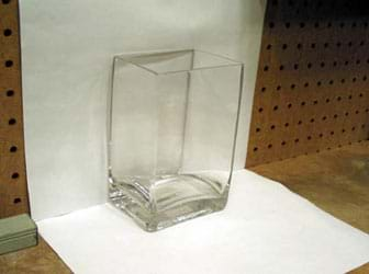Photo shows two pieces of white paper affixed to a wall and a table top to form a white background for the glass container.