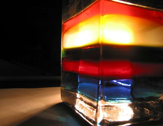 Photo shows layers of blue, red, brown, yellow and orange fluids in a glass container.