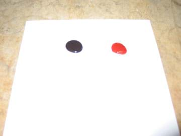 Photo shows a dark drop next to a red drop on a white piece of paper.