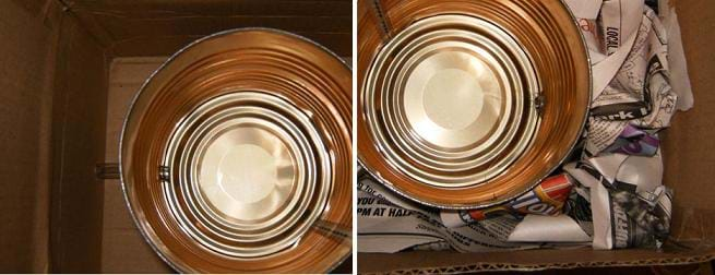 Two photos: (left) Looking down into a cardboard box at a metal coffee can at the bottom with plastic tubing visible inside and outside the container via holes in the container and box walls, (right) Looking down into a cardboard box at a metal coffee can at the bottom with crumpled newspaper stuffed into the space between the can and the box walls.