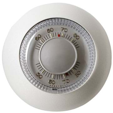 Photo shows a round, wall-mounted thermostat with a temperature dial.