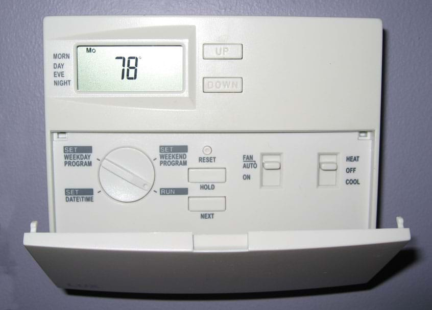 Photo shows an 11 x 9 cm plastic box mounted on a wall, displaying a temperature of 78 °F and many dials and buttons for programming temperature, dates and times.