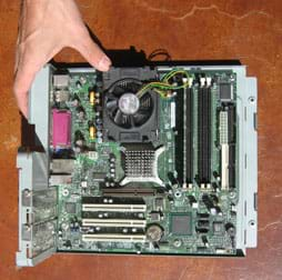Photo shows complex arrangement of circuit boards, integrated circuits, pins, wires, chips and fan pulled from inside a PC.