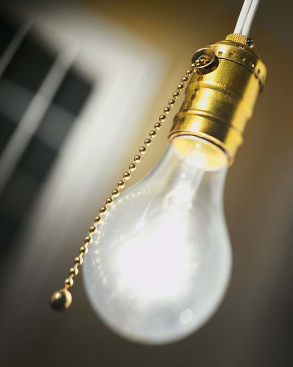 Photo shows a hanging bare light bulb with a pull cord.